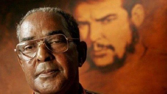 El revolucionario cubano Harry Villegas delante de un retrato de Ernesto Che Guevara